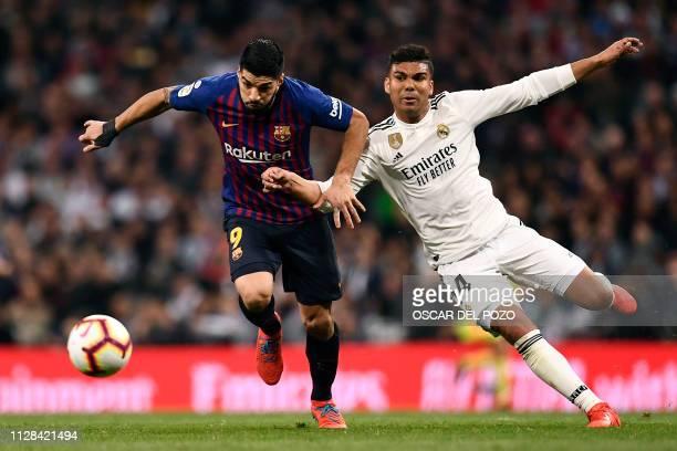 Barcelona's Uruguayan forward Luis Suarez vies with Real Madrid's Brazilian midfielder Casemiro during the Spanish league football match between Real...