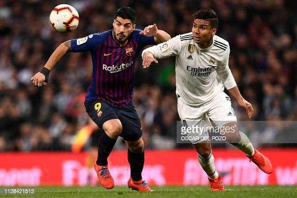 Barcelona's Uruguayan forward Luis Suarez vies with Real Madrid's Brazilian midfielder Casemiro during the Spanish league football match between Real...