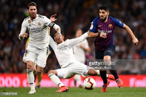 Barcelona's Uruguayan forward Luis Suarez vies with Real Madrid's Spanish defender Sergio Ramos as Real Madrid's Brazilian midfielder Casemiro falls...