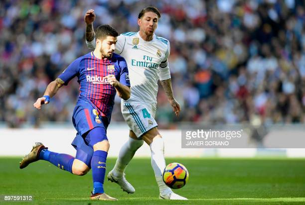 Barcelona's Uruguayan forward Luis Suarez vies with Real Madrid's Spanish defender Sergio Ramos during the Spanish League Clasico football match Real...