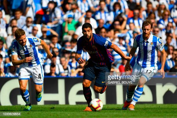 TOPSHOT Barcelona's Uruguayan forward Luis Suarez vies with Real Sociedad's Spanish midfielder Asier Illarramendi and Real Sociedad's Spanish...