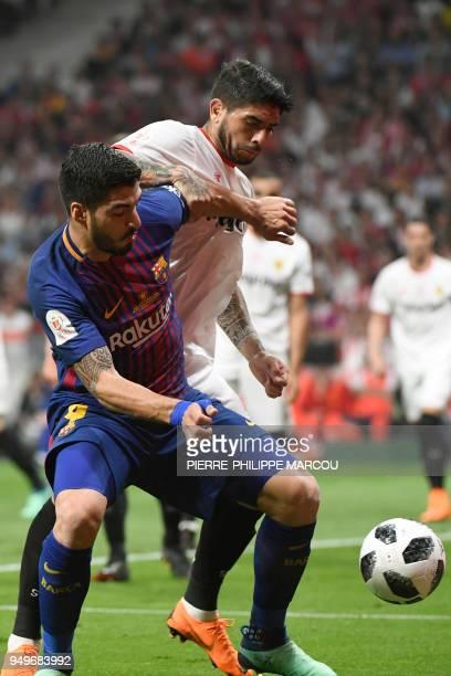 Barcelona's Uruguayan forward Luis Suarez vies with Sevilla's Argentinian midfielder Ever Banega during the Spanish Copa del Rey final football match...