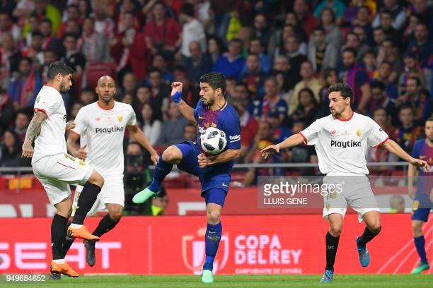 Barcelona's Uruguayan forward Luis Suarez vies with Sevilla's Argentinian midfielder Ever Banega Sevilla's French midfielder Steven N'Zonzi and...