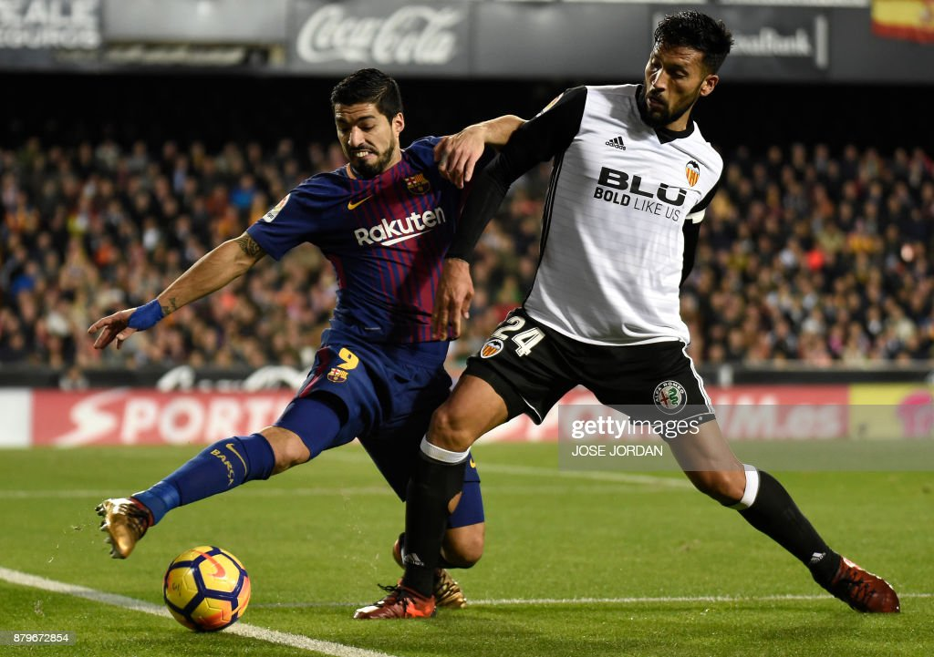 Barcelona's Uruguayan forward Luis Suarez (L) vies with Valencia's Argentinian defender Ezequiel Garay during the Spanish league football match Valencia CF and FC Barcelona at Mestalla stadium in Valencia on November 26,2017 /