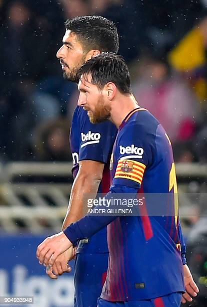 Barcelona's Uruguayan forward Luis Suarez walks with Barcelona's Argentinian forward Lionel Messi after scoring his second goal during the Spanish...