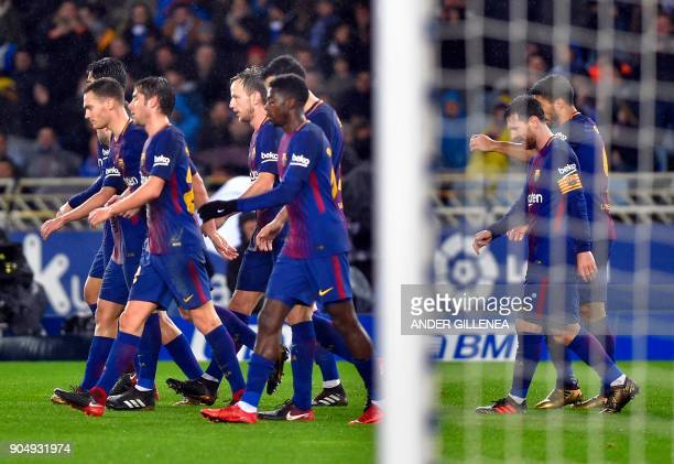 Barcelona's Uruguayan forward Luis Suarez walks with teammates after scoring his team's third goal during the Spanish league football match between...