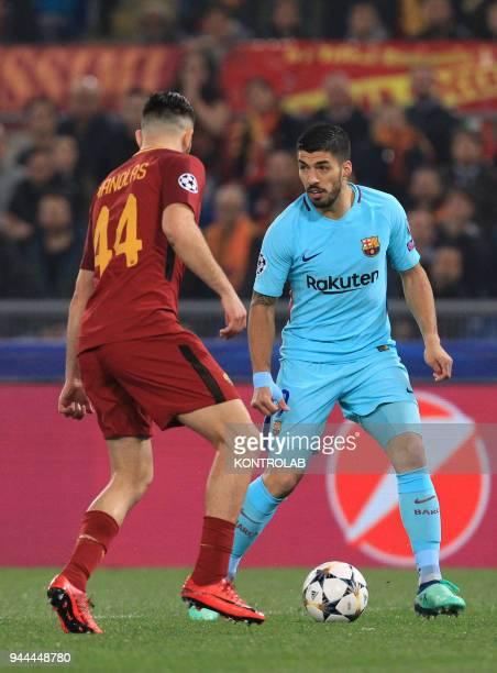 Barcelona's Uruguayan striker Luis Suarez controls the ball next to Roma's Greek defender Kostas Manolas during the UEFA Champions League...