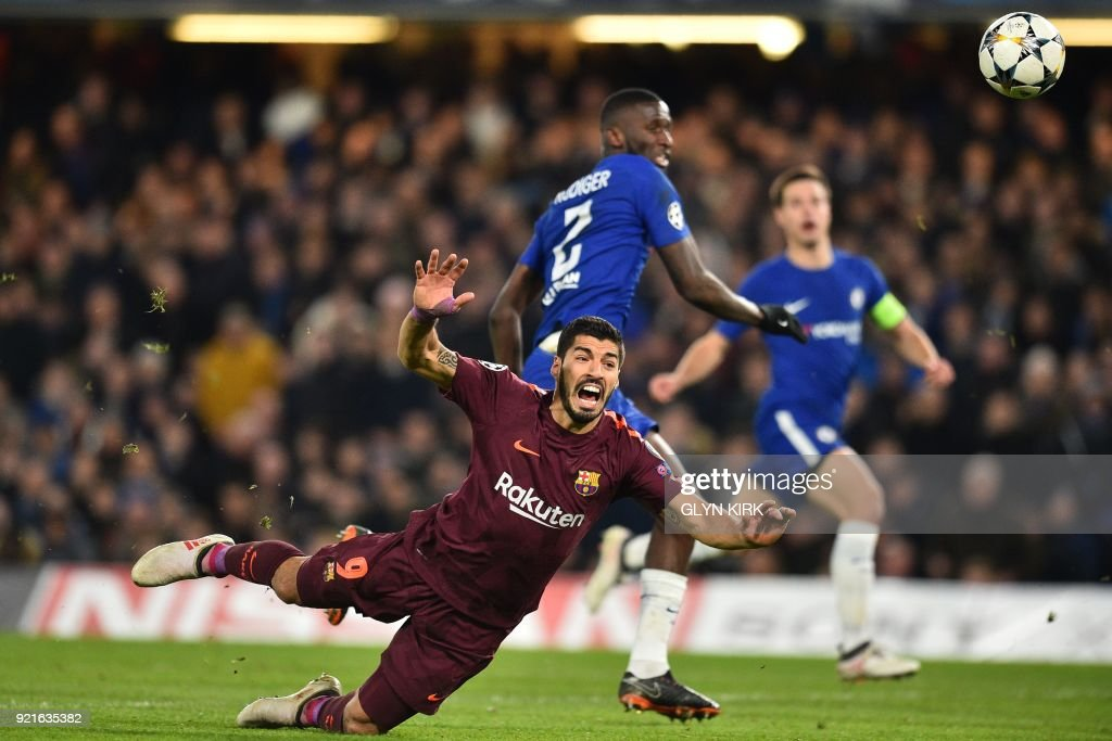 TOPSHOT - Barcelona's Uruguayan striker Luis Suarez falls to the ground after a challenge from Chelsea's German defender Antonio Rudiger during the first leg of the UEFA Champions League round of 16 football match between Chelsea and Barcelona at Stamford Bridge stadium in London on February 20, 2018. / AFP PHOTO / Glyn KIRK