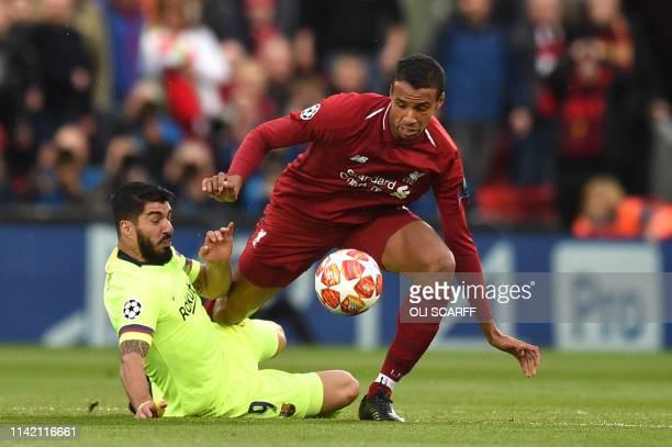 Barcelona's Uruguayan striker Luis Suarez tackles Liverpool's Germanborn Cameroonian defender Joel Matip during the UEFA Champions league semifinal...