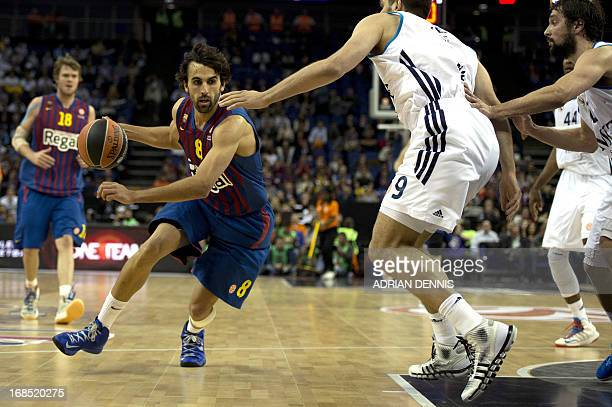 Barcelona's Victor Sada dribbles with the ball aginat Real Madrid players during their Euroleague 2013 Final Four basketball game at the O2 Arena in...