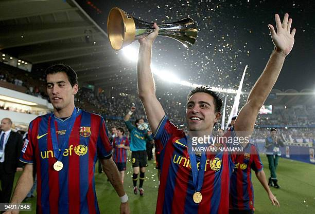Barcelona's Xavi and Sergio Busquets celebrate after winning the 2009 FIFA Club World Cup at Zayed Sports City Stadium in Abu Dhabi on December 19,...