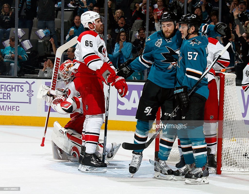 Barclay Goodrow #89, and Tommy Wingels #57 of the San Jose Sharks celebrate after Wingels' goal against Ron Hainsey #65,and Eddie Lack #31 of the Carolina Hurricanes during a NHL game at the SAP Center at San Jose on October 24, 2015 in San Jose, California.