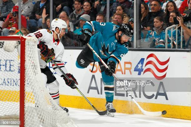 Barclay Goodrow of the San Jose Sharks keeps the puck away from Jordan Oesterle of the Chicago Blackhawks at SAP Center on March 1 2018 in San Jose...