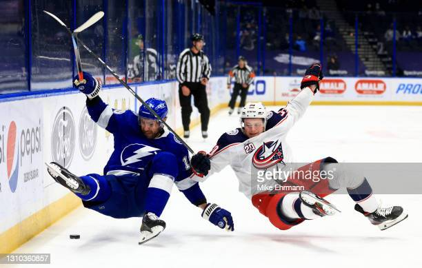 Barclay Goodrow of the Tampa Bay Lightning and Eric Robinson of the Columbus Blue Jackets fights for the puck during a game at Amalie Arena on April...