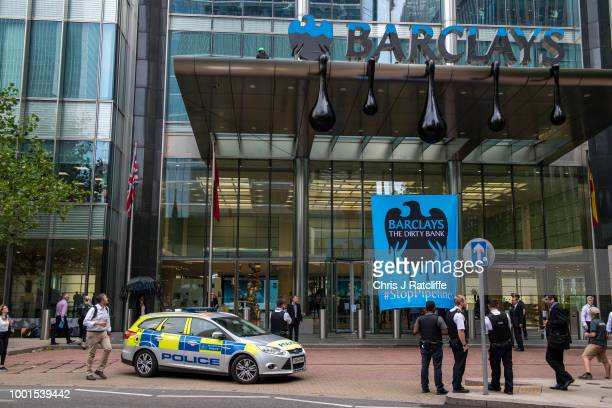 Barclays employees queue to enter the building whilst Greenpeace activists redress the main entrance in an oil drip effects as they scale Barclays...