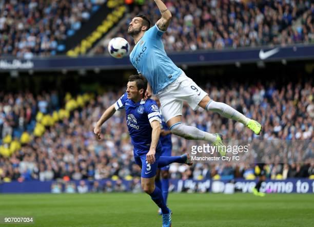 Barclays Premier League Manchester City v Everton Etihad Stadium Manchester City's Alvaro Negredo and Everton's Leighton Baines battle for the ball...