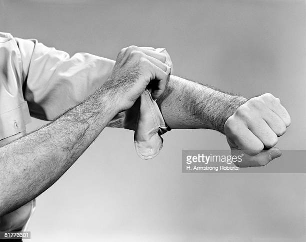bare arm & hand rolling up the sleeve of the clenched fist right arm hairy worker robust. - long sleeved stock pictures, royalty-free photos & images