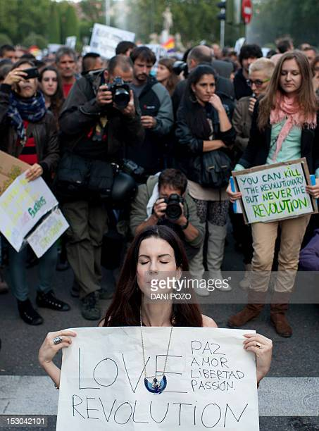 A bare breast protester holds a placard reading Love unites us we are all equal we were born free and we will die free during a demonstration...