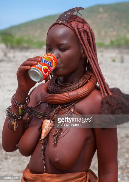 Bare breasted himba woman drinking fanta epupa Namibia on March 3 2014 in Epupa Namibia