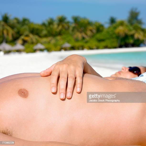 bare chest lying on beach - barechested bare chested ストックフォトと画像