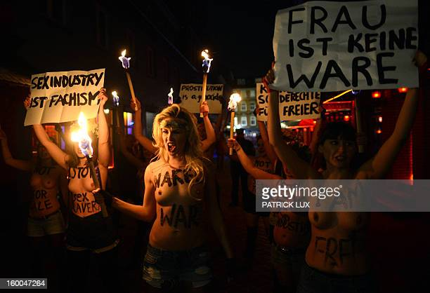 "Bare chested activists of Femen, a Ukranian feminist movement, hold torches and a banner that reads ""A woman is not a commodity"" to protest against..."