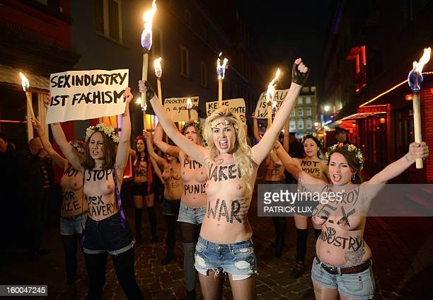 Bare chested activists of Femen, a Ukranian feminist movement, hold torches as they protest against prostitution in the red light district...