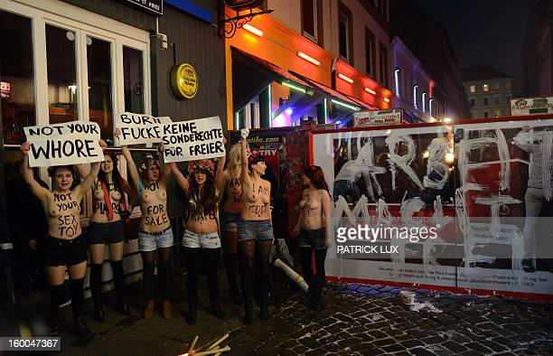Bare chested activists of Femen a Ukranian feminist movement protest against prostitution next to a slogan Work makes you free painted on the...