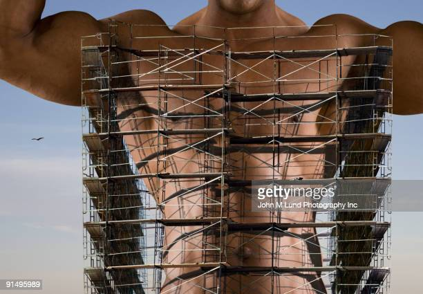 Bare chested African man with scaffolding around torso