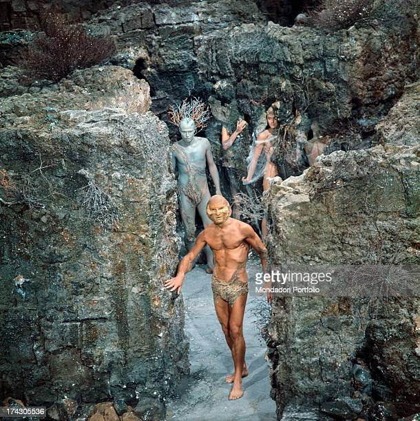 A bare chested athletic man with a mask stands on a rocky scenery with other characters playing in Barbarella all of them have fancy and coloured...