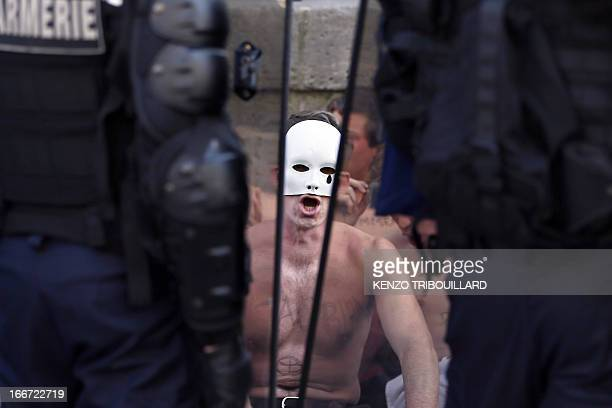Bare chested demonstrator, member of the anti-gay marriage group Hommen, sits in front of riot police as they try to block one of Paris's main street...