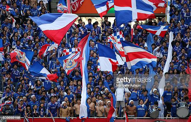 Bare chested fans of Yokohama Marinos at the front of the supporters block with the rest waving flags