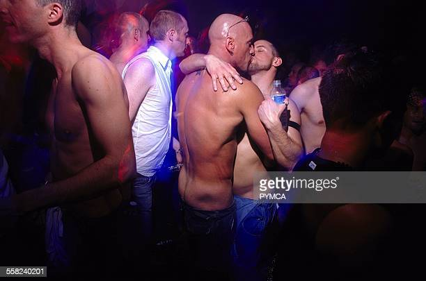 Bare chested male couple kissing amongst the crowd at Crash night Yoko Ono performance London March 2002