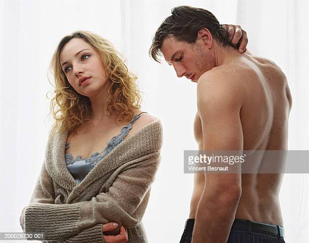 Bare chested man beside young woman wrapped in cardigan
