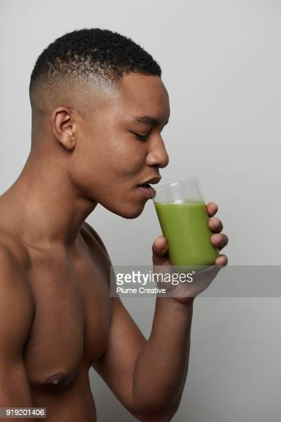bare chested man drinking a green juice - bare chested man foto e immagini stock
