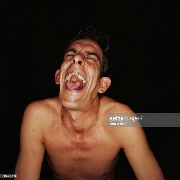 Bare chested man laughing, close-up