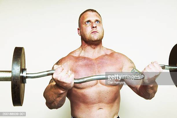 bare chested man lifting barbell, looking upwards - barechested bare chested ストックフォトと画像