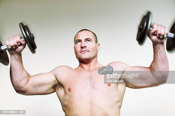 bare chested man lifting dumbbells, looking upwards (blurred motion) - chest barechested bare chested foto e immagini stock