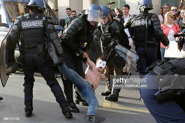 Bare chested man, member of the anti-gay marriage group Hommen, is arrested by riot police as they try to block one of Paris's main street on April...