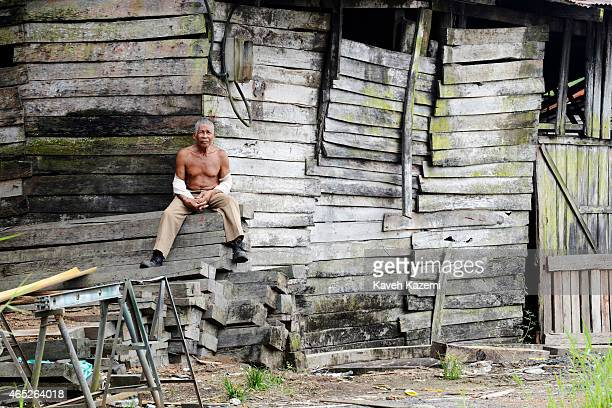 Bare chested man sits on wooden planks of wood outside a wood workshop in La Playita neighborhood on January 15, 2015 in Buenaventura, Colombia....