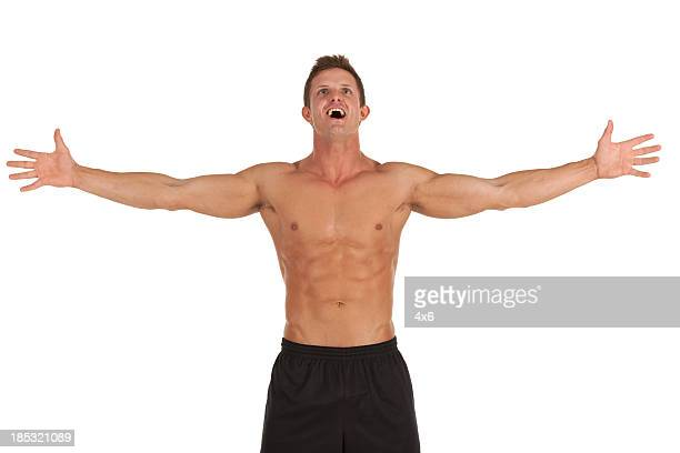 Bare chested man standing with arms extended