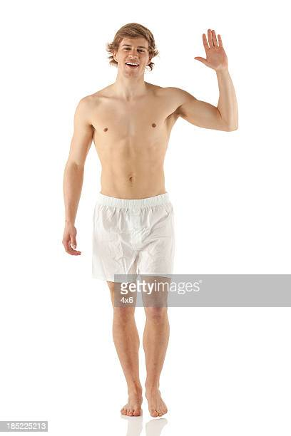 Bare chested man walking and waving hand
