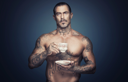 Bare chested man with tattoos holding a cup of tea. 466519781