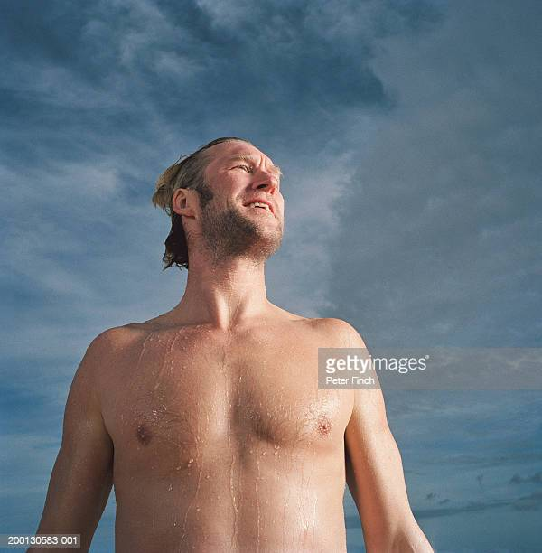 bare chested man with wet hair, low angle view - chest barechested bare chested imagens e fotografias de stock