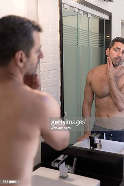 bare chested mature man looking in mirror, hand on chin, touching stubble - chest barechested bare chested foto e immagini stock