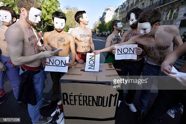 Bare chested men sporting white masks and belonging to an anti-gay group perform a mock vote to demonstrate against a bill legalizing same sex...