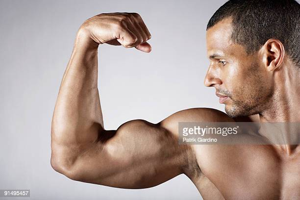 Bare chested mixed race man flexing biceps