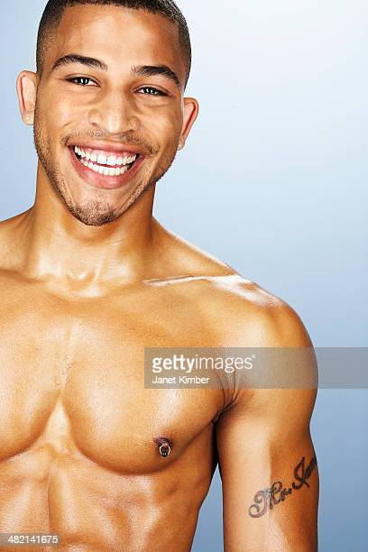 bare chested mixed race man smiling - brustwarzen piercing stock-fotos und bilder