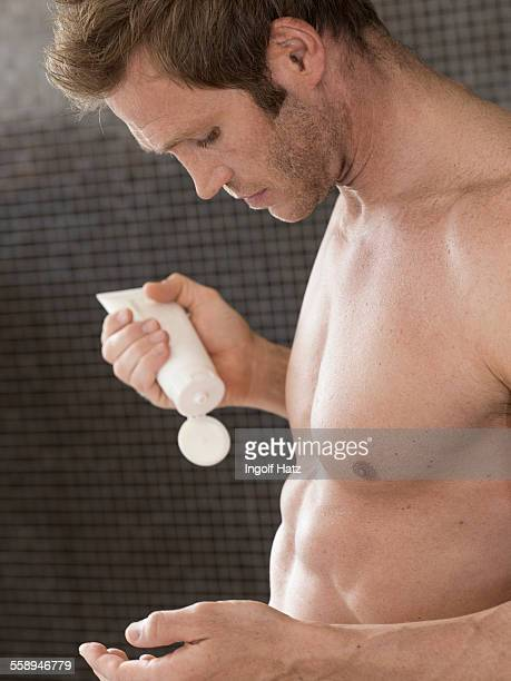 Bare chested muscular man in bathroom applying moisturizer