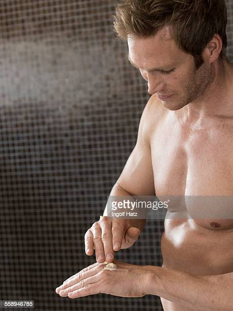 Bare chested muscular man in bathroom rubbing in hand cream