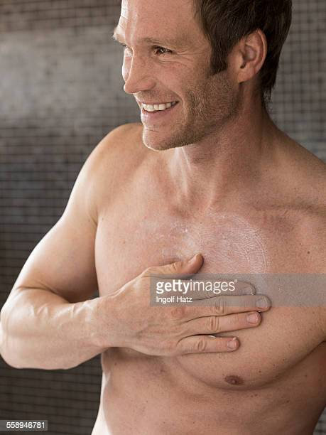 Bare chested muscular man in bathroom rubbing moisturizer on chest